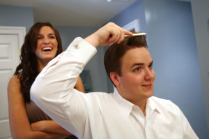 Groom getting ready for his wedding ceremony with the help of the maid of honor in Annandale, Virginia