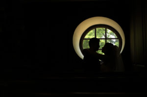 Bride and groom are silhouetted in a window in the Wren Chapel in Williamsburg, Virginia