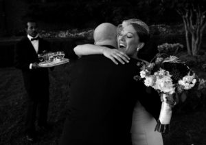 Bride gets hugs during a receiving line before her wedding reception at Oxon Hill Manor in Oxon Hill, Maryland.