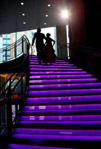 Bride and Groom walk up steps heading to their wedding reception